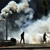 Des étudiants soutenant le président islamiste déchu Mohamed Mosri en Egypte au milieu de fumées de gaz lacrymogènes tirés par la police pour disperser une manifestation le 26 mars 2014 au Caire