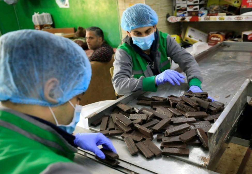 Des employés dans des usines d\'Al-Arees manipulent des biscuits au chocolat dans la ville de Gaza, le 5 février 2020