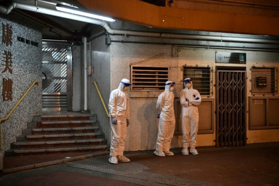 Du personnel médical en combinaison de protection devant l\'entrée d\'une tour d\'habitation après la découverte d\'un second cas du nouveau coronavirus dans cette résidence, le 11 février 2020 à Hong Kong