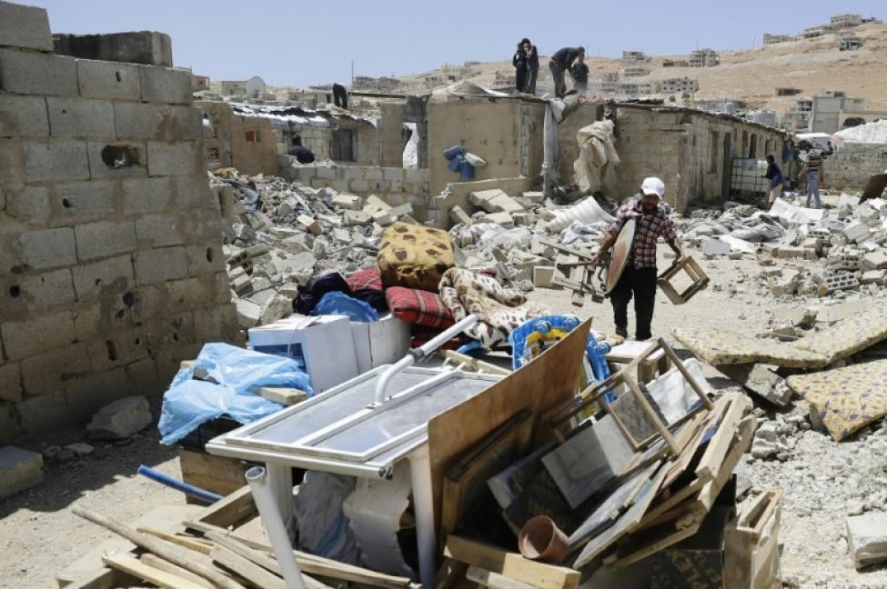 Un Syrien rassemble ses affaires alors que des travailleurs détruisent des abris construits en béton dans un camp de réfugiés syriens à Arsal, dans le nord-est du Liban, le 10 juin 2019
