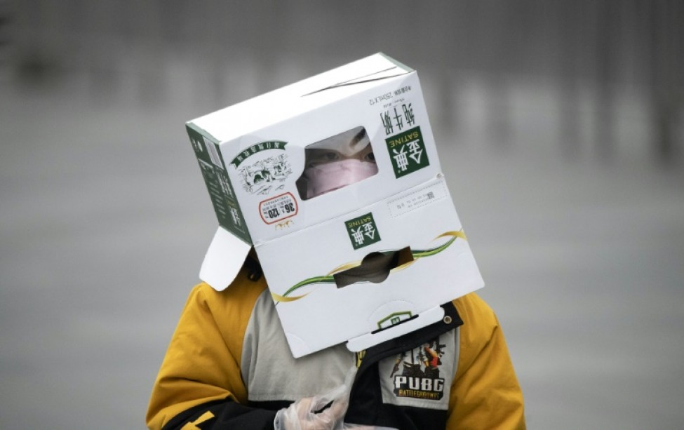 A boy wears a cardboard box on his head at a railway station in Shanghai