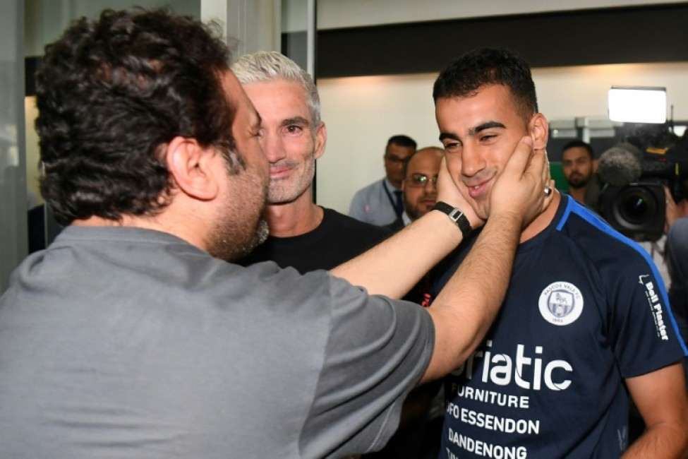 Hakeem al-Araibi (R) was greeted by a crowd of supporters including former Australian football captain Craig Foster (C) who led a campaign for his release