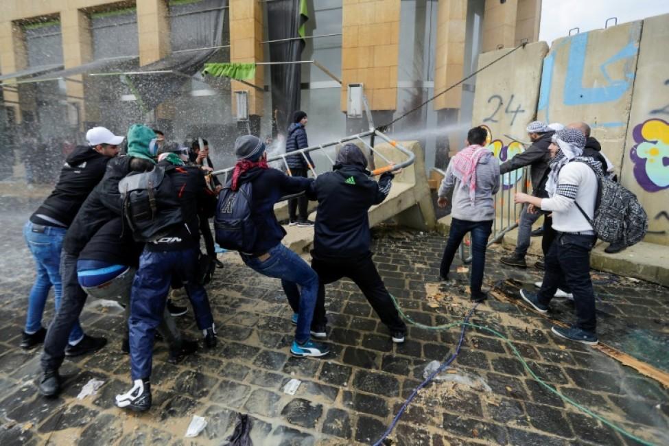 Des manifestants anti-gouvernementaaux s'en prennent à une section des blocs de ciment protégeant les institutions de l'Etat dans le centre de Beyrouth lors des manifestations du 11 février 2020 pour empêcher un vote de confiance en faveur d'un nouveau gouvernement