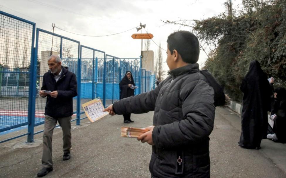 Un Iranien distribue des prospectus électoraux à l\'extérieur d\'une mosquée dans la capitale iranienne Téhéran, le 14 février 2020