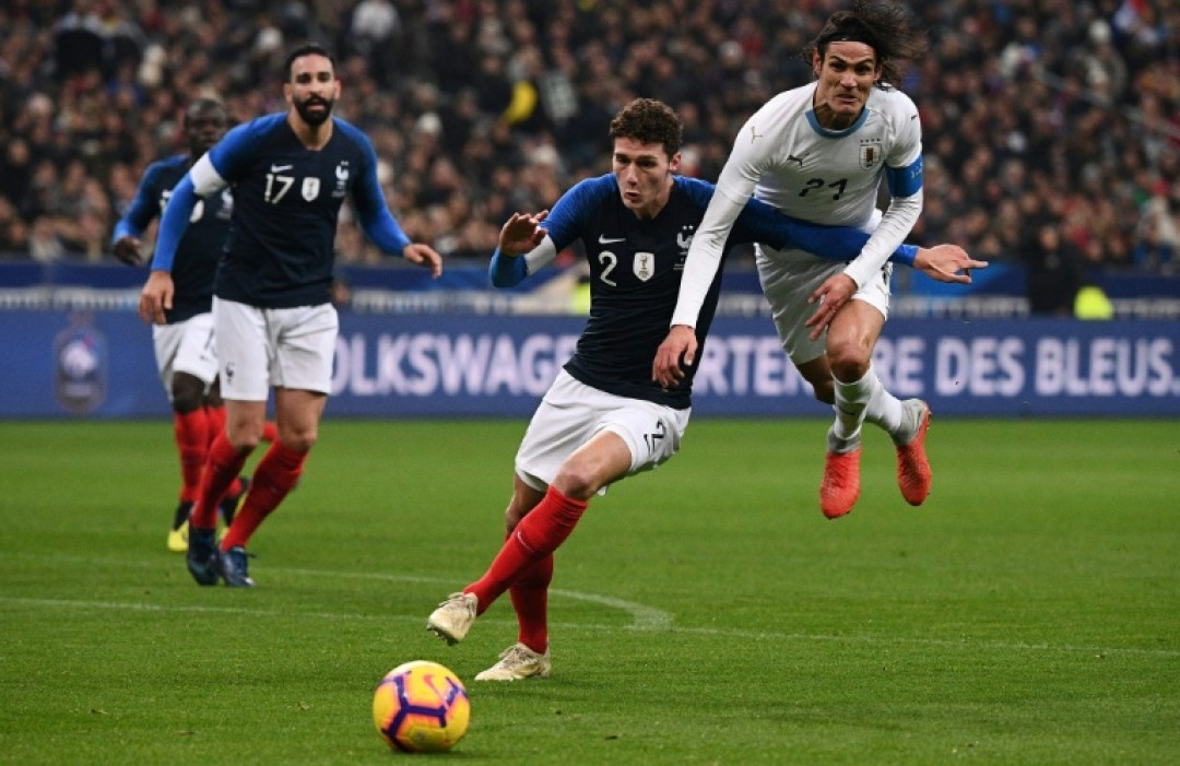 France defender Benjamin Pavard (C) vies with Uruguay forward Edinson Cavani during a November 20 friendly at the Stade de France.