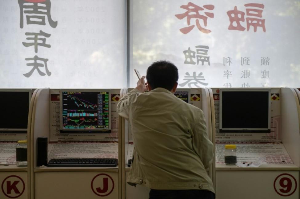 Les cours des actions sont affichés dans une société de placement à Pékin, le 11 octobre 2018