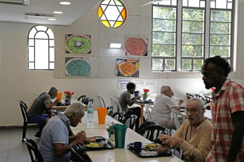 Des hommes déjeunent au centre Lasova, \