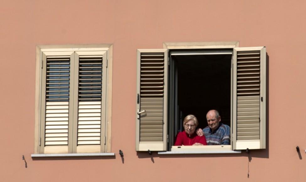 Un couple à sa fenêtre écoute la messe des Rameaux célebrée en face de chez lui sur le toit d\'une église à Rome, le 5 avril 2020