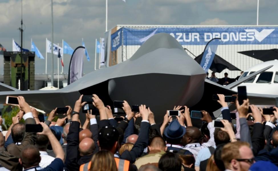 Des visiteurs assistent à la présentation d\'une maquette grandeur nature du futur avion de combat européen du programme SCAF (système de combat aérien du futur), à l\'aéoport du Bourget, près de Paris, le 17 juin 2019