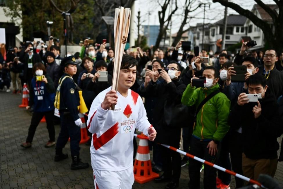 Un homme tient la flamme olympique lors d\'une répétition à Tokyo de la cérémonie d\'ouverture des Jeux olympiques 2020, le 15 février 2020