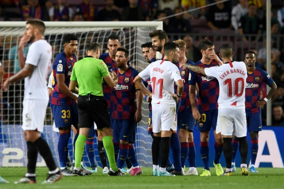 Referee Mateu Lahoz, who sent off Ronald Araujo, No. 33, received advice from Lionel Messi and Luis Suarez as well as several Sevilla players