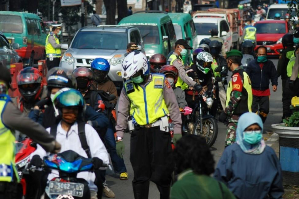 Des policiers contrôlent des motocyclistes se rendant dans leur village natal pour fêter l\'Aïd el-Fitr, le 22 mai 2020 à Bandung (Indonésie)