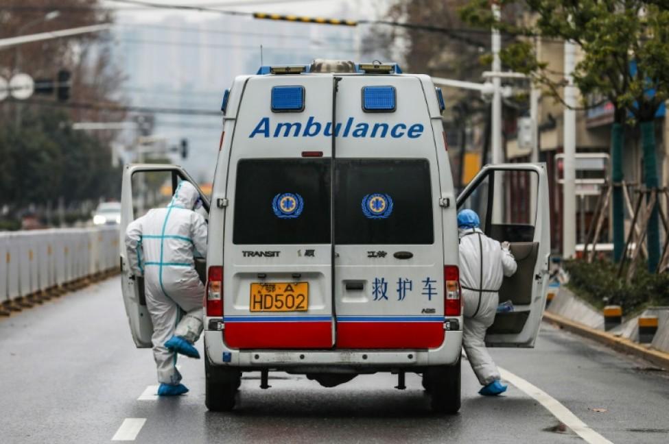 Une ambulance et son personnel sanitaire circule dans les rues de Wuhan, le 26 janvier 2020