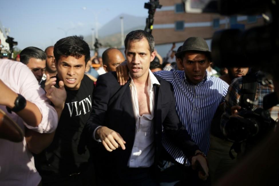 Juan Guaido (c), chef de l\'opposition vénézuélienne reconnu comme président par intérim par près de 60 pays, est escorté vers un véhicule par ses partisans après son arrivée à l\'aéroport de Maiqueta, près de Caracas, le 11 février 2020
