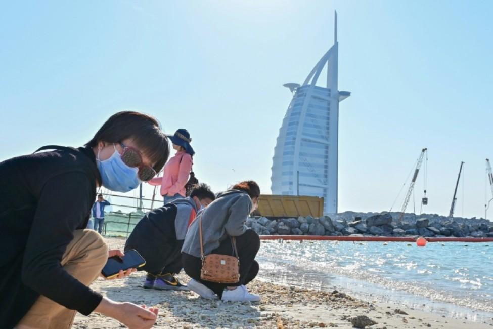 Des touristes portant des masques chirurgicaux cherchent des coquillages sur une plage à Dubaï, le 29 janvier 2020