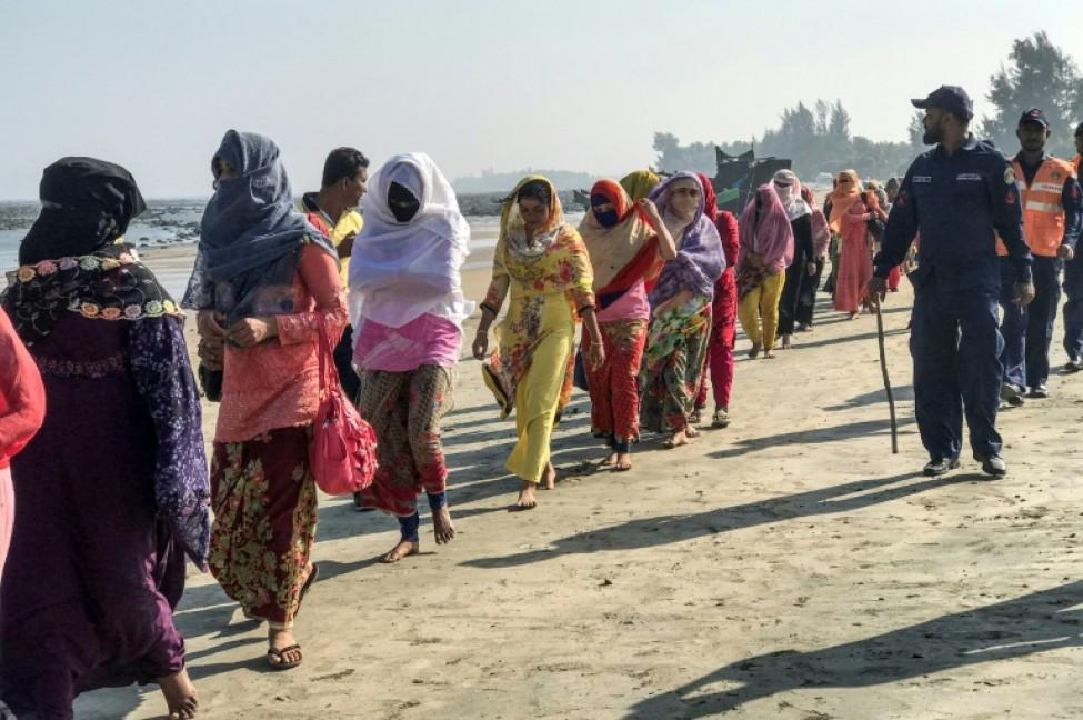 Des gardes-côtes escortent des réfugiés rohingyas après le naufrage de leur bateau à Teknaf (Bangladesh), le 11 février 2020