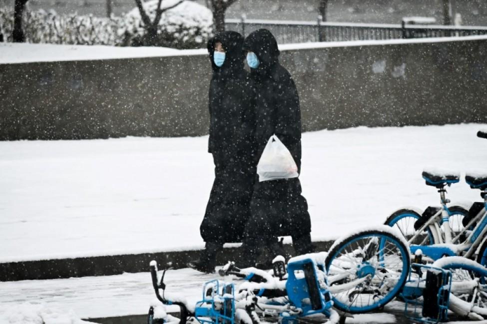 Deux femmes avec des masques de protection marchent le long d\'une route à Pékin, le 14 février 2020