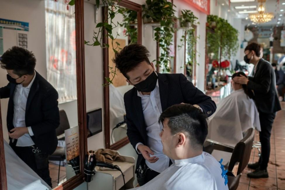 Des coiffeurs portent un masque de protection dans un salon de Pékin le 23 janvier 2020