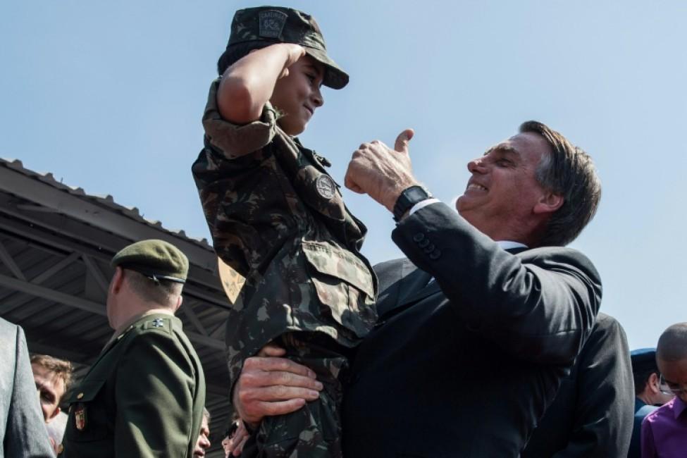 Photo archive du 3 mai 2018 montrant le candidat à la présidentielle brésilienne Jair Bolsonaro tenant un enfant en uniforme militaire à Sao Paulo