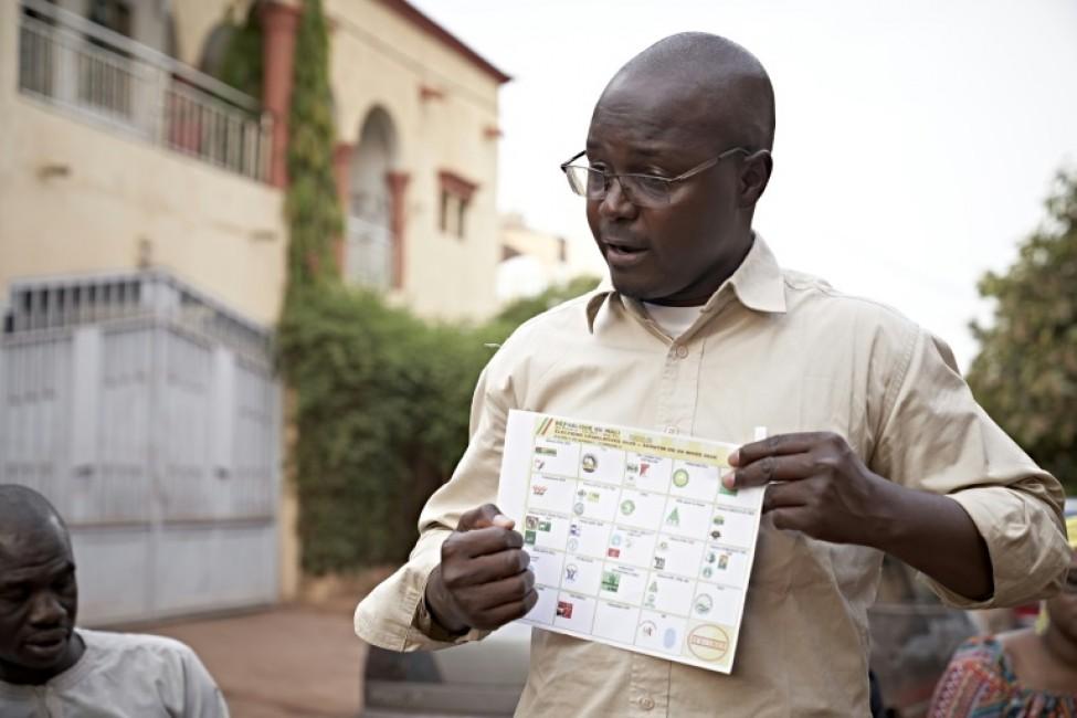 Le candidat Amadou Kone montre un document de vote, le 23 marS 2020 à Bamako, lors de sa campagne électorale pour les législatives au Mali