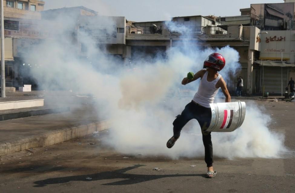Casque de moto sur la tête, un Irakien court pour échapper aux gaz lacrymogènes, lors d\'une manifestation contre le pouvoir, à Bagdad le 7 novembre 2019