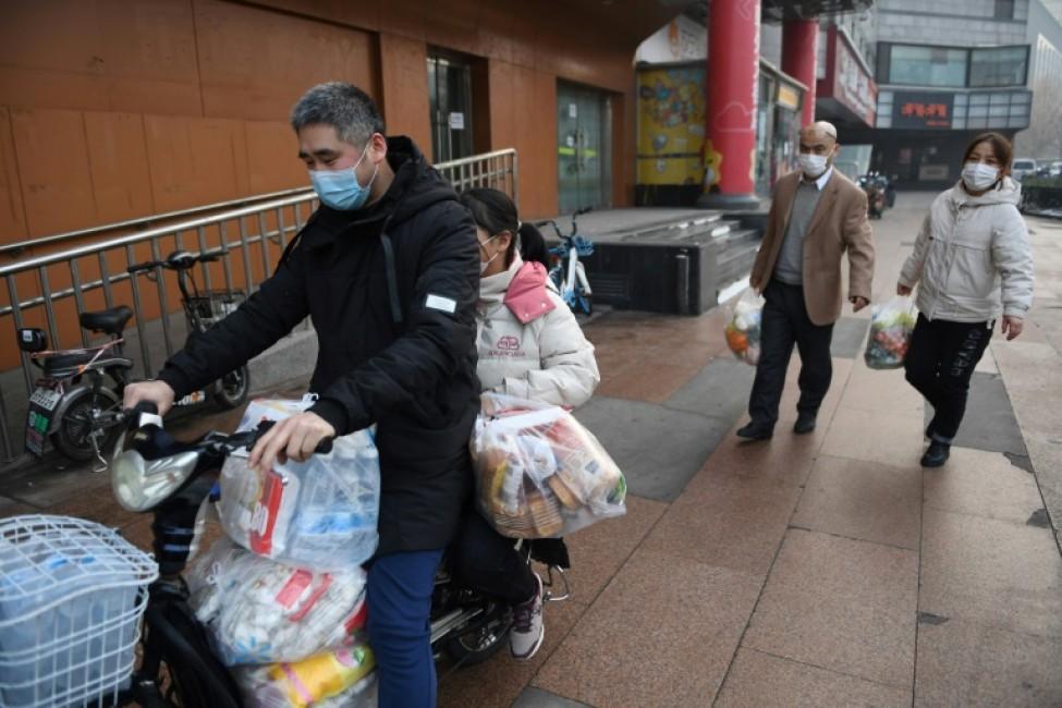 Des habitants portant des masques de protection rentrent chez eux avec des sacs de provisions, le 11 février 2020 à Pékin, en cHINE