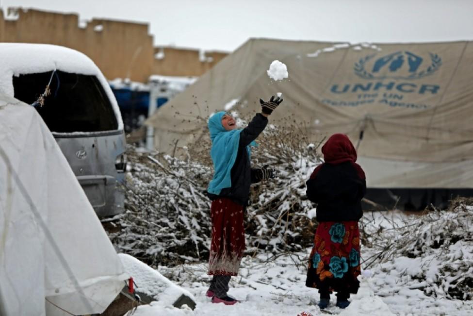 Des enfants ayant fui les combats jouent avec la neige dans un camp de déplacés, près de la ville syrienne de Tal-Abyad, à la frontière avec la Turquie, le 13 février 2020