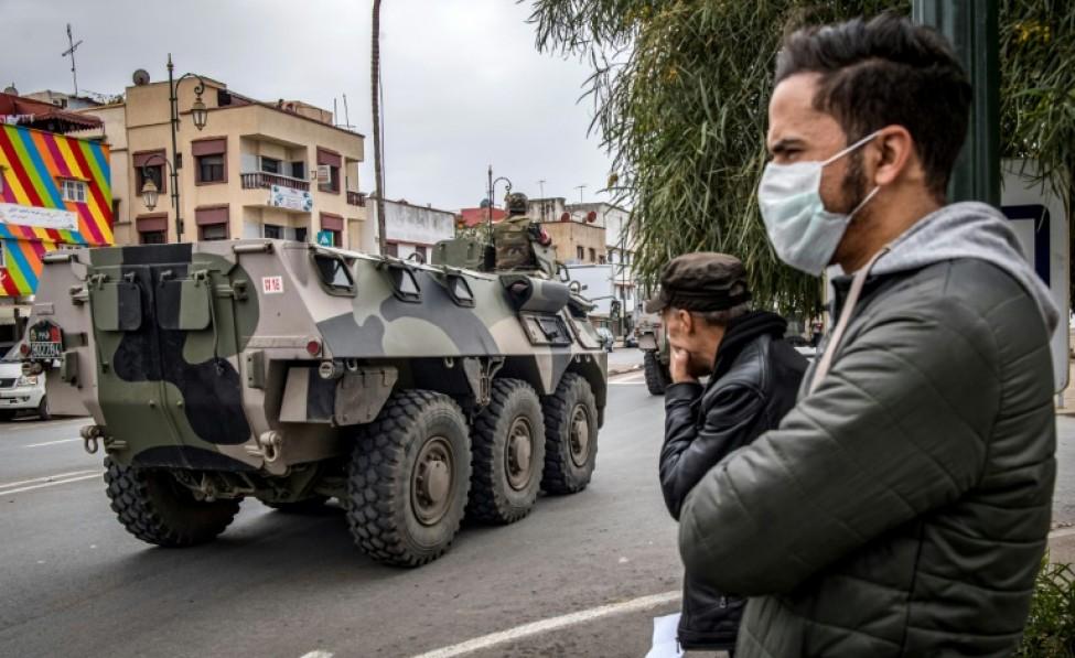 Deux hommes regardent passer un char de l\'armée marocaine enjoignant les habitants de Rabat à rester chez eux face au nouveau coronavirus, le 22 mars 2020