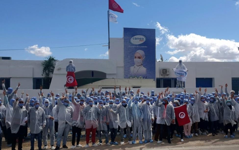 Photo distribuée le 26 mars 2020 par l\'entreprise Consomed montrant les employés devant l\'usine où ils se sont confinés pour fabriquer des masques de protection contre le nouveau coronavirus, à Kairouan (centre)