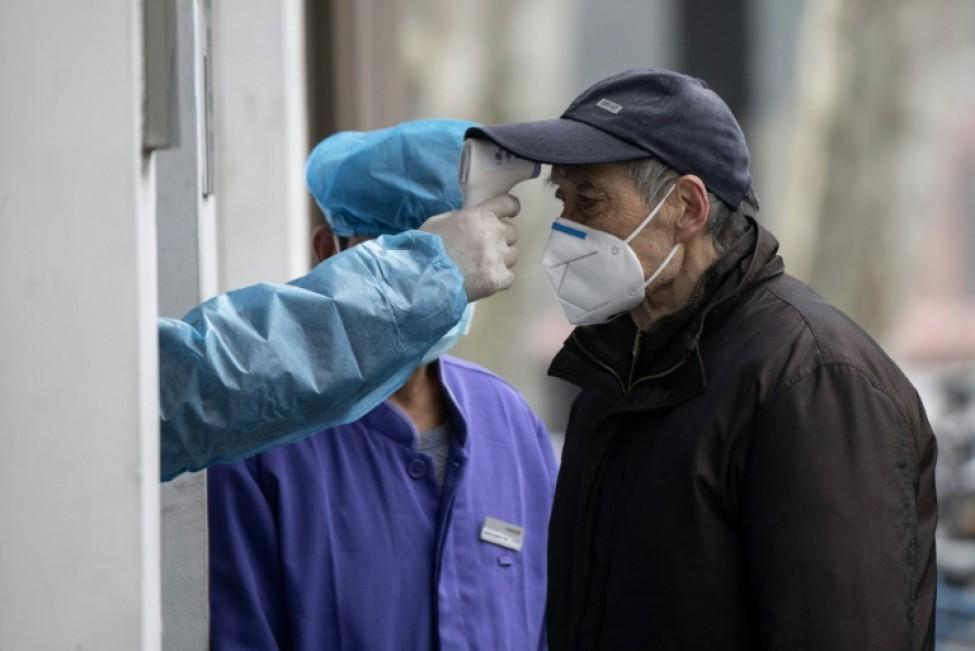 La température d\'un homme est vérifiée le 13 février à devant l\'entrée d\'un hôpital à Shanghai