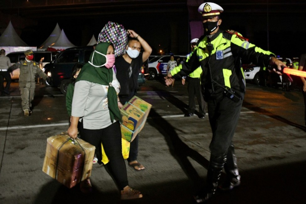 Des Indonésiens voulant rentrer dans leur village natal pour fêter l\'Aïd el-Fitr se voient ordonner par la police de rentrer à Jakarta, le 23 mai 2020 à Cikarang (Indonésie)