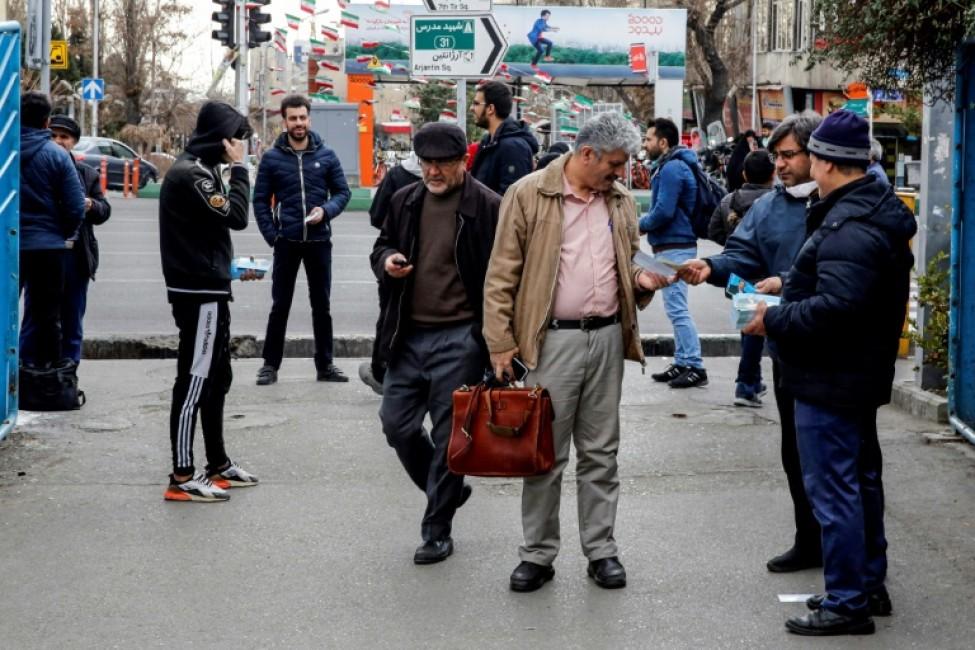 Des Iraniens distribuent des prospectus électoraux à l\'extérieur d\'une mosquée dans la capitale iranienne Téhéran, le 14 février 2020