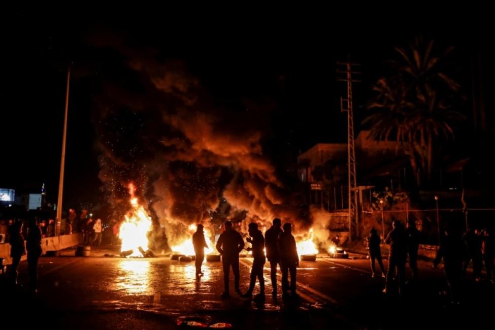 Des manifestants libanais devant des pneus enflammés, sur une route allant de Beyrouth à Byblos, le 21 janvier 2020