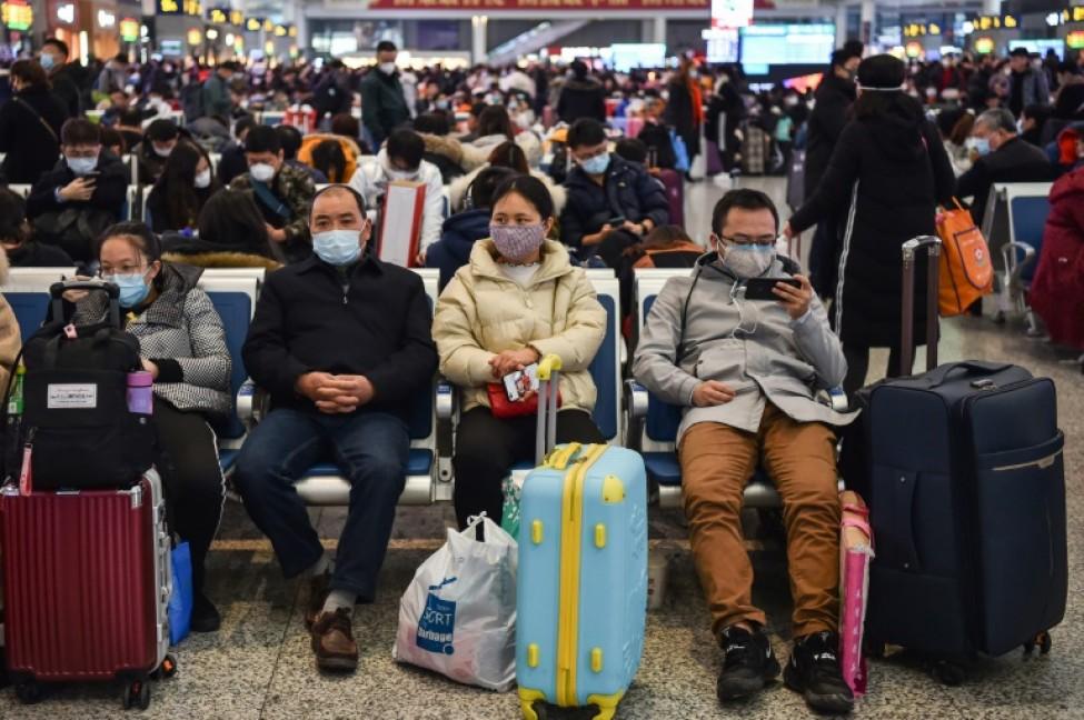 Des passagers équipés de masques de protection attendent leur train pour aller voir leur famille à l\'occasion du Nouvel An chinois, à Shanghai le 23 janvier 2020