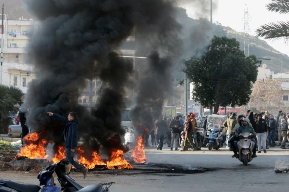 Des manifestants antigouvernementaux libanais brûlent des pneus lors d\'une manifestation dans la ville de Tripoli, dans le nord du pays, le 14 janvier 2020