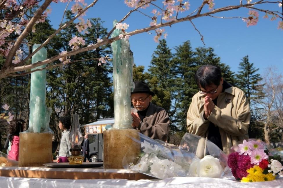 Des personnes se recueillent devant un autel dédié aux victimes du tsunami de 2011 dans un parc de Tokyo, le 11 mars 2020 au Japon