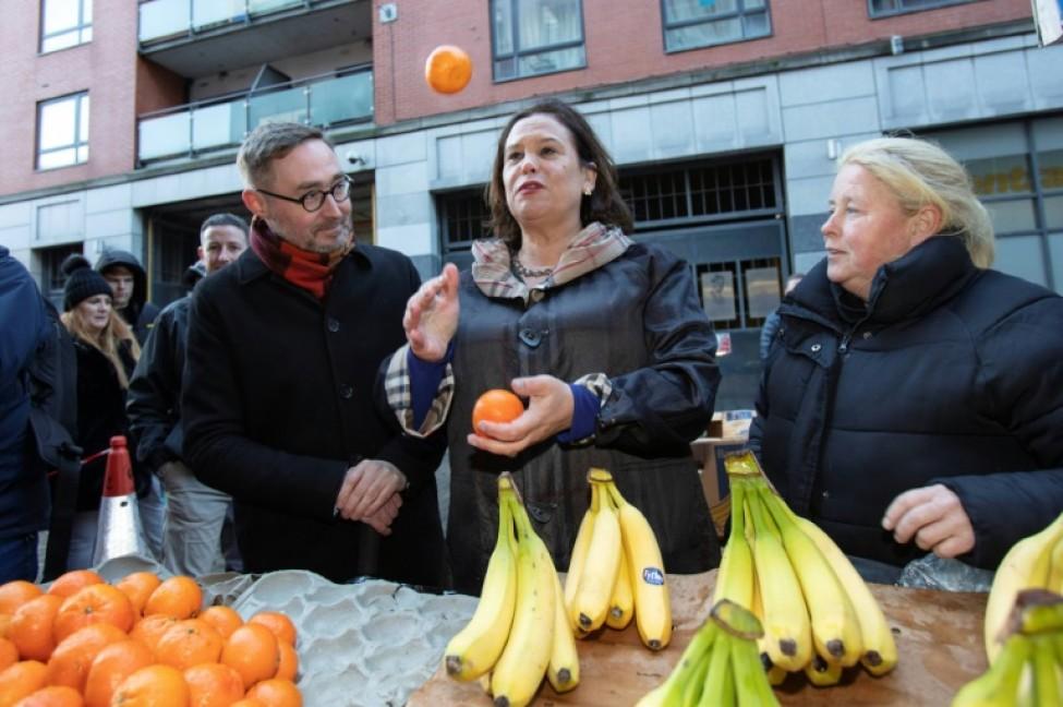 Mary Lou McDonald (c), la cheffe du Sin Fein, jongle avec des oranges en parlant avec une vendeuse de fruits (d), le 10 février 2020 à Dublin