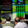 Des investisseurs surveillent le cours des actions à Shangai, en Chine, le 25 septembre 2018