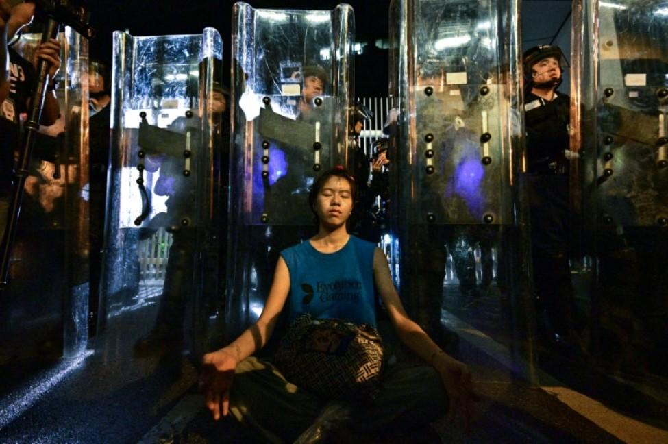 Une femme médite devant les forces de l\'ordre, le 12 juin 2019 à Hong Kong
