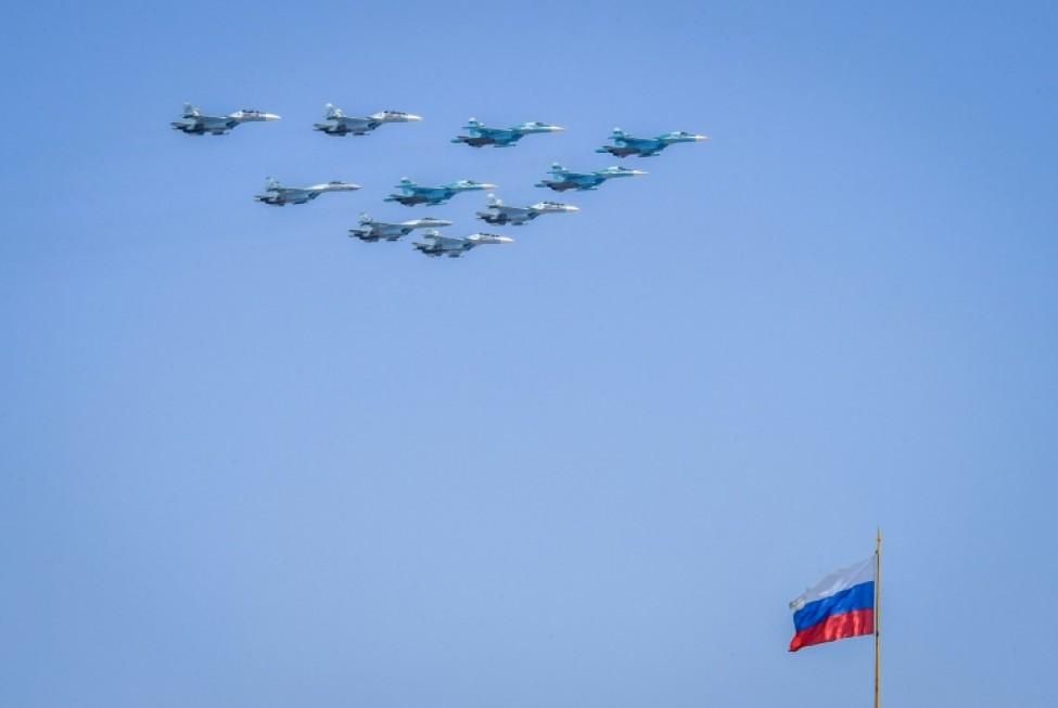 Des avions militaires Soukhoï Su-35 et Su-34 survolent le drapeau national russe au-dessus de la place du Kremlin à Moscou, le 7 mai 2019, durant une répétition pour la parade célébrant le 74e anniversaire de la victoire sur l\'Allemagne nazie le 9 mai 1945.