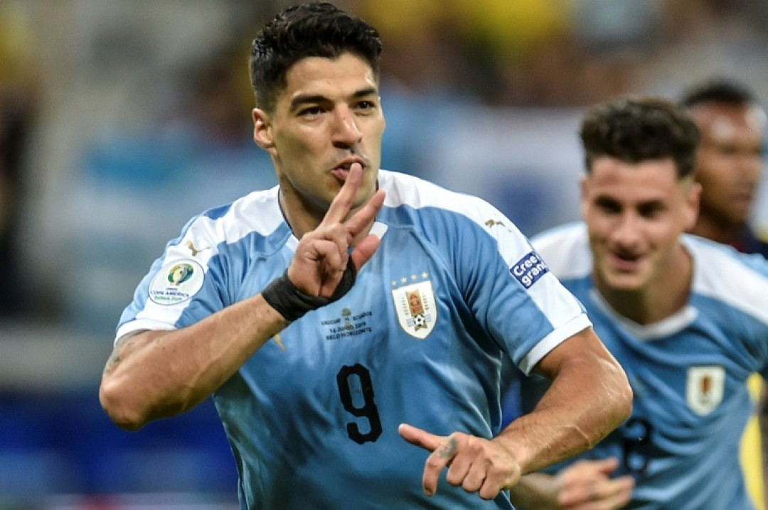Luis Suarez wheels away in celebration after netting Uruguay\'s third goal following a flick-on by Martin Caceres
