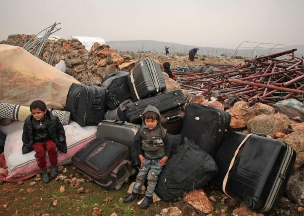 Des enfants syriens qui ont fui l\'ouest de la province d\'Alep sont assis sur des valises dans un camp de fortune installé sur des ruines près d\'Atareb, le 19 janvier 2020