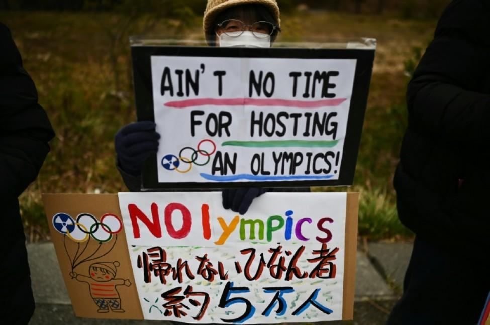 Un manifestant tient une pancarte dénonçant le départ de la flamme olympique depuis le J-Village, à Naraha près de Fukushima, le 29 février 2020