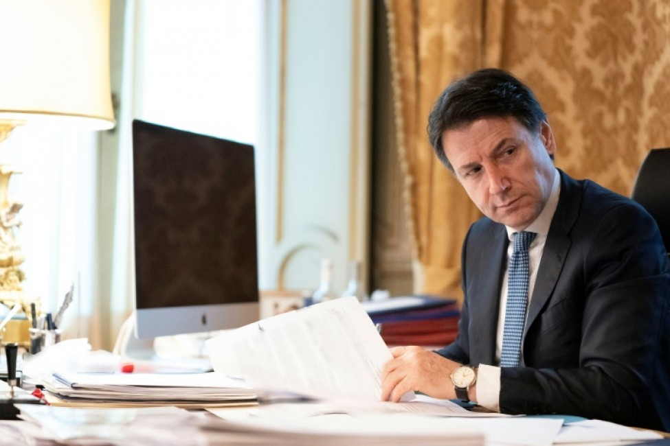 Photo en date du 26 mars 2020 transmise par les services de presse du Palais Chigi, résidence officielle du Premier ministre italien à Rome, montrant le chef du gouvernement italien Giuseppe dans son bureau