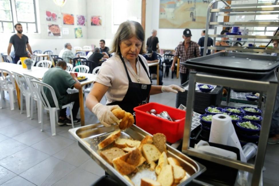 Une femme dispose du pain sur le buffet du centre Lasova, \